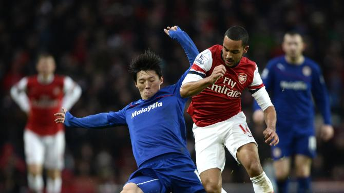 Arsenal's Walcott challenges Cardiff City's Kim during their English Premier League soccer match in London