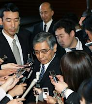 New Bank of Japan Governor Haruhiko Kuroda (C) is surrounded by reporters after his appointment by Prime Minister Shinzo Abe at the latter's office in Tokyo, on March 21, 2013. Kuroda, a finance veteran who backs aggressive easing measures to drag Japan out of its malaise, told Abe he would do his best to help right the world's third-largest economy