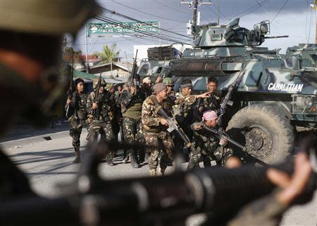 Government soldiers take cover on armoured vehicles as they try to assault the positions of Muslim rebels from the Moro National Liberation Front (MNLF), during a gunbattle in Zamboanga city in southern Philippines September 13, 2013. REUTERS/Erik De Castro