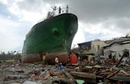 People walk amongst debris next to a ship washed ashore in the aftermath of Super Typhoon Haiyan at Anibong in Tacloban, eastern island of Leyte on November 11, 2013