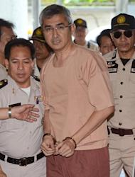 Thai 'Red Shirt' leader and member of parliament, Korkaew Pikulthong, is escorted by police upon his arrival at a criminal court in Bangkok, on December 13, 2012. A separate terrorism case against 24 'Red Shirt' leaders, including five current lawmakers, over their part in rallies from two years ago was again postponed on December 13 after two witnesses failed to attend