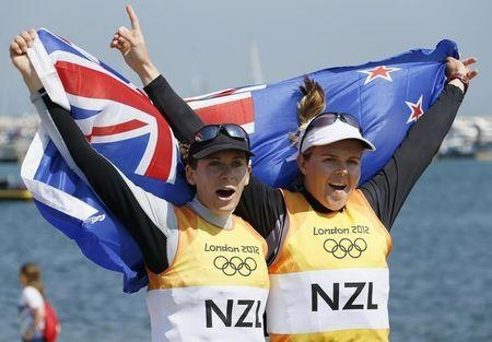New Zealand's Jo Aleh and Olivia Powrie celebrate as they arrive in the harbour after winning gold in the women's 470 sailing class at the London 2012 Olympic Games