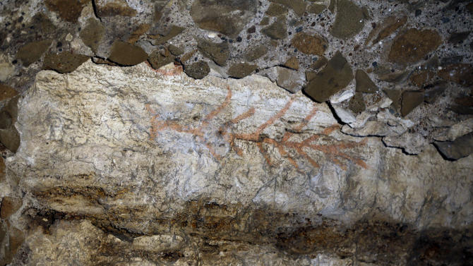An ancient graffiti recently discovered during restoration works is seen inside a gallery of Rome's Colosseum, Friday, Jan. 18, 2013. A long-delayed restoration of the Colosseum's only intact internal passageway has yielded ancient traces of red, black and blue frescoes — as well as graffiti and drawings of phallic symbols — indicating that the arena where gladiators fought was far more colorful than previously thought. Officials unveiled the discoveries Friday and said the passageway would be open to the public starting this summer, after the €80,000 ($100,000) restoration is completed. The frescoes were hidden under decades of calcified rock and grime, and were revealed after the surfaces were cleaned. The traces confirmed that while the Colosseum today is a fairly monochrome gray travertine rock, red brick and bits of moss-covered marble, in its day its interior halls were a rich and expensive Technicolor. (AP Photo/Gregorio Borgia)