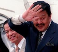 This file photo shows then President Joseph Estrada (R) escorted by Filipino-Chinese tycoon Lucio Tan, in 1999, before leaving Manila for a foreign visit. Tan has won a decades-long legal battle to keep the fortune he built up during the dictatorship of Ferdinand Marcos, according to his lawyer