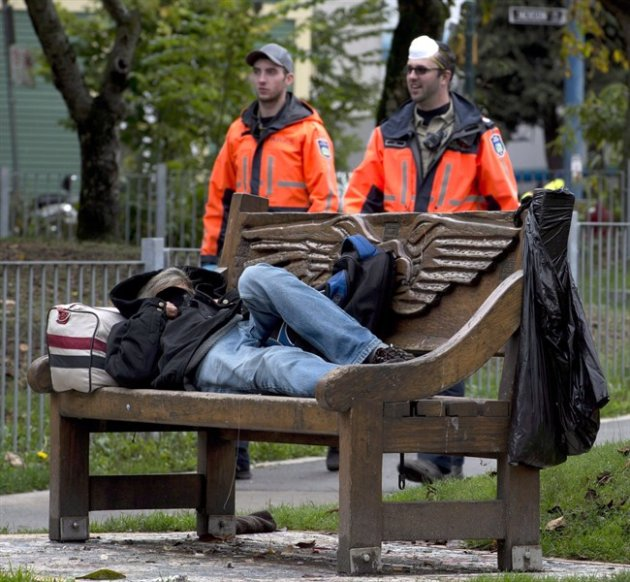 Park rangers walk past a homeless person sleeping on a bench in Vancouver's Oppenheimer Park.