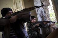 Rebel fighters aim their weapons at regime forces on the front line in the Old City of Aleppo, on December 21, 2012. Syrians woke up to air strikes near Damascus on New Year's Day as Aleppo airport was closed after repeated rebel attacks, casting doubts on diplomatic drives to end the 21-month conflict.