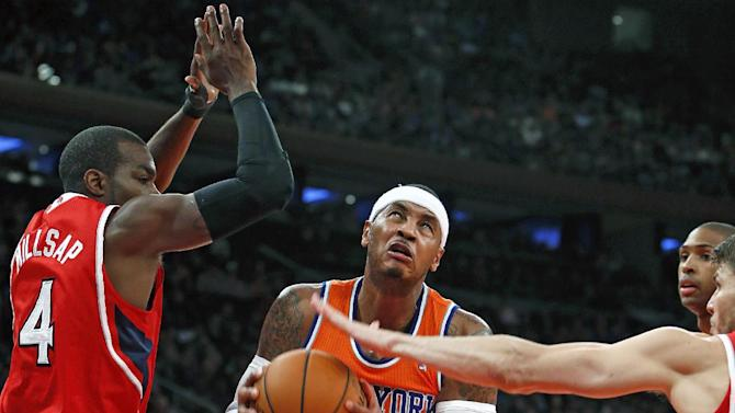 New York Knicks' Carmelo Anthony, center, goes to the basket against a double team from Atlanta Hawks' Paul Millsap (4) and Kyle Korver, right, during the first half of an NBA basketball game Saturday, Nov. 16, 2013, in New York.  Atlanta defeated New York 110-90