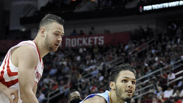 Denver Nuggets' Evan Fournier, right, is grabbed by Houston Rockets' Donatas Motiejunas in the first half of an NBA basketball game Saturday, Nov. 16, 2013, in Houston