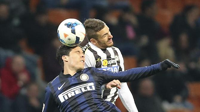 Inter Milan Brazilian midfielder Anderson Hernanes, left, jumps for the ball with Udinese defender Silvan Widmer, of Switzerland, during the Serie A soccer match between Inter Milan and Udinese at the San Siro stadium in Milan, Italy, Thursday, March 27, 2014