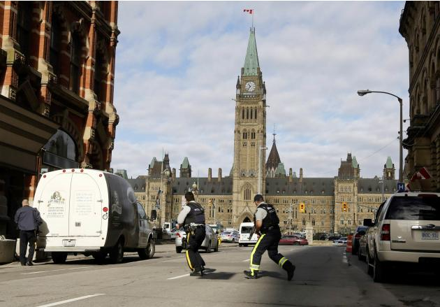 Armed RCMP officers race across a street on Parliament Hilll following a shooting incident in Ottawa