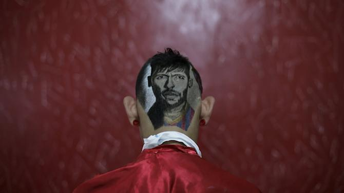Fernadez, poses with an image of Barcelona's Neymar shaved on his head, at a barbershop run by hair artist and barber Nariko in Sao Vicente, near Santos, in Sao Paulo state