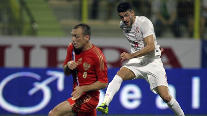 Serbia's Filip Djordevic, right, shoots the ball as Russia's Denis Glushakov defends during a friendly match Dubai, United Arab Emirates, Friday Nov. 15, 2013