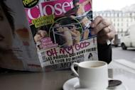 Un hombre lee el número de la revista francesa Closer que publica las fotos en toples de la duquesa Catalina de Cambridge, esposa del príncipe Guillermo de Inglaterra, este viernes en un café de París. (AFP | Kenzo Tribouillard)