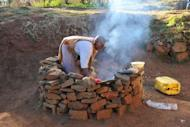 Mampai Lesgapa, 62, cooks in front of her home in the village of Ha Seoehlana in May 2012. Lesgapa was resettled for the Mohale Dam in 2002