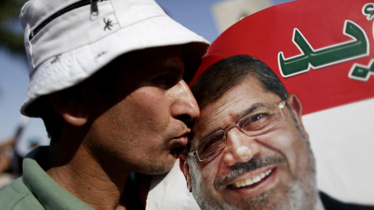 A man kisses a poster with the photograph of Egypt's Islamist President Mohammed Morsi during a rally, in Nasser City, Cairo, Egypt, Wednesday, July 3, 2013. Egypt's military moved to tighten its control on key institutions Wednesday, even putting officers in the newsroom of state TV, in preparation for an almost certain push to remove the country's Islamist president when an afternoon ultimatum expires.(AP Photo/Hassan Ammar)