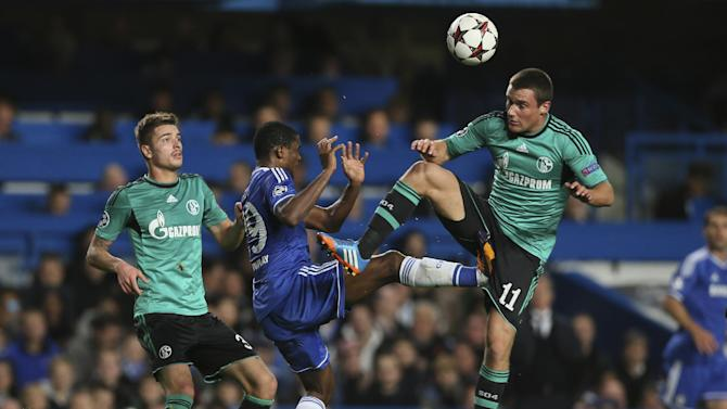 Chelsea's Samuel Eto'o makes contact with Schalke's Christian Clemens, No.11  during the Champions League group E soccer match between Chelsea and FC Schalke 04 at Stamford Bridge stadium in London, Wednesday, Nov. 6, 2013