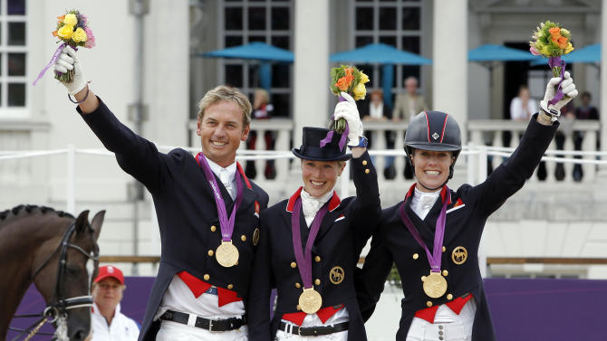 Gold medallists Britain's Carl Hester, Laura Bechtolsheimer and Charlotte Dujardin hold up their bouquets at equestrian dressage team victory ceremony at London 2012 Olympic Games in Greenwich Park