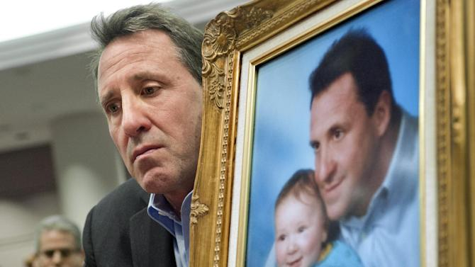 Neil Heslin, holding a picture of himself with his son Jesse, testifies at the Legislative Office Building in Hartford, Conn., Monday, Jan. 28, 2013. Heslin, whose 6-year-old son Jesse Lewis was one of the 20 first-graders killed in the Dec. 14 massacre at Sandy Hook Elementary School in Newtown, Conn. , told a legislative subcommittee reviewing gun laws that there is no need for such weapons in homes or on the streets. (AP Photo/Jessica Hill)