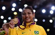 Brazil's Sarah Menezes poses on the podium with her gold medal at the London 2012 Olympics on July 28. Menezes revealed Sunday that her parents tried to stop her from taking up the sport which they believed was for men only. The 22-year-old from Brazil became the first woman from her country to win an Olympic judo gold