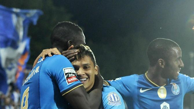 FC Porto's Juan Quintero, centre, celebrates with Jackson Martinez, both from Colombia, and Ricardo Pereira, right, after scoring from a free kick against Arouca during their Portuguese League soccer match at the Municipal Stadium, in Arouca, Portugal, Sunday Oct. 6, 2013. Jackson scored twice and Quintero once in Porto's 3-1 victory