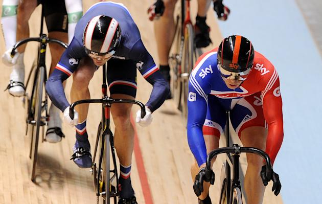 Chris Hoy of Britain (R) crosses the finish line ahead of Mickael Bourgain of France (L) to win his second round heat in the men's keirin as Scott Sunderland of Australia (L) looks on at the 2012