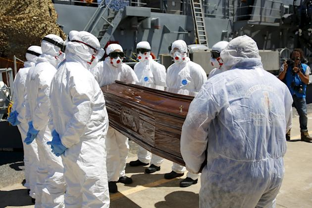 A coffin, containing the body of an unidentified migrant, is carried off the Irish Navy ship LE Niamh in the Sicilian harbour of Messina