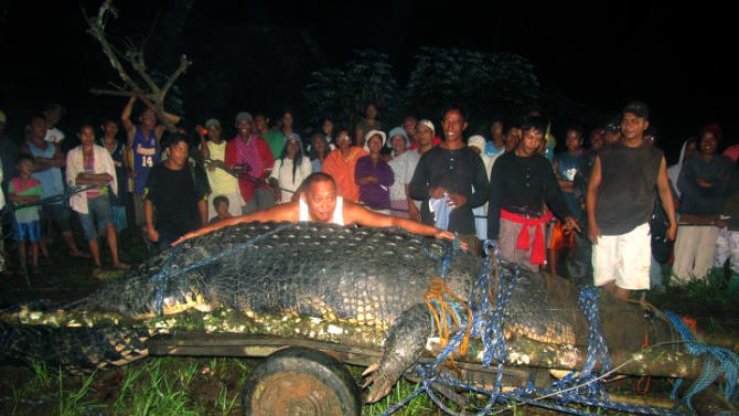 In this Sept. 4, 2011 file photo, residents watch as Mayor Cox Elorde of Bunawan township, Agusan del Sur province, pretends to measure a huge crocodile, later named