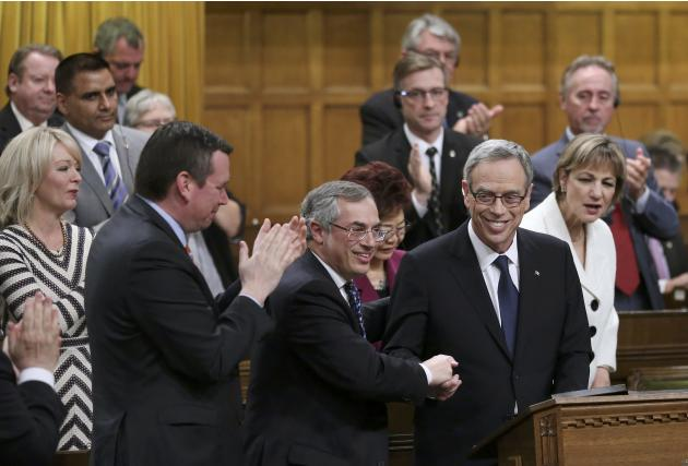 Canada's Finance Minister Joe Oliver shakes hands with MP Tony Clement after he delivered the federal budget in the House of Commons on Parliament Hill in Ottawa