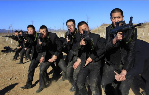 Students holding replica 95 semi-automatic rifles practice protecting their employers at a shooting training field managed by the military during the Tianjiao Special Guard/Security Consultant trainin