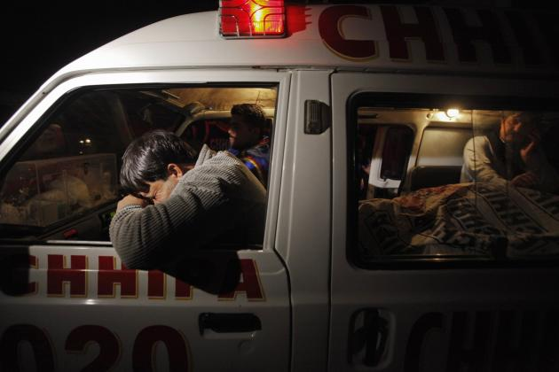 A relative (L) mourns his family member, who was killed by unknown gunmen, next to his body in an ambulance, outside the Civil Hospital morgue in Karachi February 9, 2014. At least six people were killed, including a young child, after unknown gunmen opened fire in Karachi's Baldia Town, local media reported. REUTERS/Akhtar Soomro (PAKISTAN - Tags: CIVIL UNREST CRIME LAW)