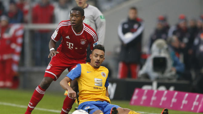 Bayern's David Alaba of Austria, top, and Braunschweig's Karim Bellarabi challenge for the ball during the German first division Bundesliga soccer match between FC Bayern Munich and Eintracht Braunschweig, in Munich, southern Germany, Saturday, Nov. 30, 2013