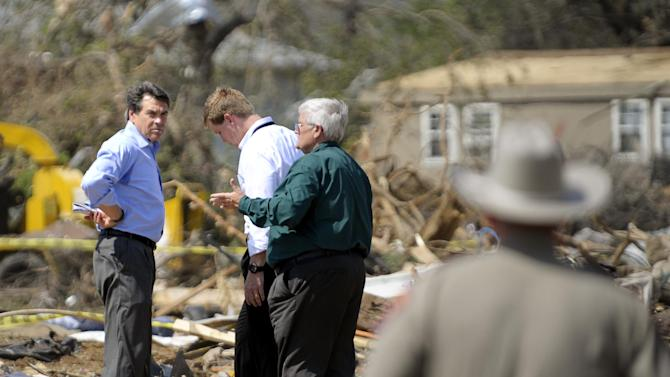 Texas Governor Rick Perry, left, tours the storm-damaged Rancho Brazos Estates subdivision near Granbury, Texas, on Friday May 17, 2013. On Wednesday, powerful storms produced 16 tornadoes in the area that left six dead. (AP Photo/The Fort Worth Star-Telegram, Max Faulkner)  MAGS OUT; (FORT WORTH WEEKLY, 360 WEST); INTERNET OUT