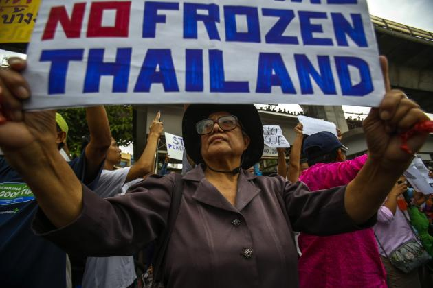 A demonstrator holds up a sign as she joins others during a protest against military rule at Victory Monument in Bangkok May 27, 2014. Thailand's military rulers settled down to work at their Bangkok headquarters on Tuesday, firmly in charge with royal endorsement while rounding up critics and searching for weapons they fear could still be used to fight their takeover. REUTERS/Athit Perawongmetha (THAILAND - Tags: POLITICS CIVIL UNREST MILITARY)