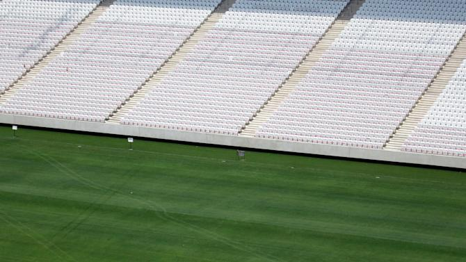 A workman installing grass in the Arena Sao Paulo stadium walks across the pitch as construction continues in Sao Paulo