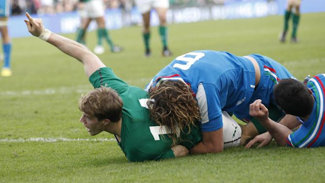 Ireland's Andrew Trimble left, scores a try despite being tackled by Italy's Joshua Raffaele Furno during their Six Nations Rugby Union international match at the Aviva Stadium, Dublin, Ireland, Saturday, March 8, 2014. (AP Photo/Peter Morrison)
