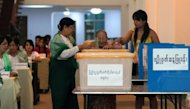 An elderly woman casts her vote at a polling station in Yangon on April 1, 2012