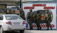 Armed men, believed to be Russian servicemen, gather at a tyre assembling shop outside the naval headquarters in Sevastopol, March 19, 2014. REUTERS/Vasily Fedosenko