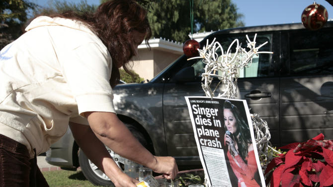 A fan lights a candle outside the home of singer Jenni Rivera's mother in Lakewood, Calif. Monday, Dec. 10, 2012. Rivera died Sunday in a plane crash in Mexico. U.S. authorities confirmed Monday that Jenni Rivera, a U.S.-born singer whose soulful voice and openness about her personal troubles made her a Mexican-American superstar, was killed Sunday in a plane crash in northern Mexico. (AP Photo/Jason Redmond)