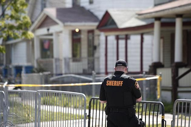 A police officer keeps the public away from the house where three women, who disappeared as teens about a decade ago, were found alive May 7, 2013 in Cleveland, Ohio. The Internet exploded with virtual cheers Tuesday for the colorful US dishwasher who helped three young women flee a decade in captivity