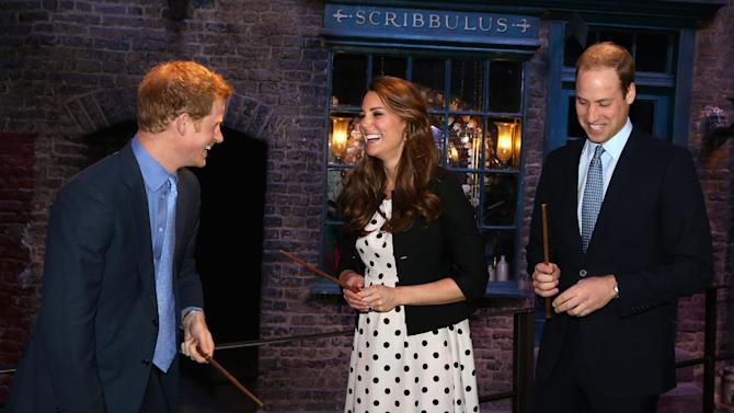 "Britain's Kate the Duchess of Cambridge with her husband Prince William, right, and his brother Prince Harry hold their wands on the film set used to depict Diagon Alley in the Harry Potter Films during the inauguration of ""Warner Bros. Studios Leavesden"" near Watford, approximately 18 miles north west of central London, Friday, April 26, 2013. As well as attending the inauguration Friday at the former World War II airfield site, the royals will undertake a tour of Warner Bros. ""Studio Tour London - The Making of Harry Potter"", where they will view props, costumes and models from the Harry Potter film series. (AP Photo/Chris Jackson, Pool)"