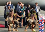 Britain's Prince William (centre L) and his wife Catherine, the Duchess of Cambridge receive a traditional welcome from Island Warriors following their arrival at the airport in Honiara on September 16, 2012