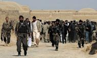 An Afghan delegation walks with locals after a gathering for a memorial ceremony at a mosque in Alokozai village in Panjwayi district, Kandahar province, on March 13, 2012. Gunmen on Tuesday attacked the memorial service for 16 villagers killed by a US soldier, shooting dead a member of the Afghan military and wounding a policeman in a hail of gunfire