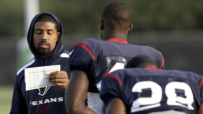 Houston Texans running back Arian Foster, left, reads off practice assignments to teammates during NFL football training camp Tuesday, July 29, 2014, in Houston