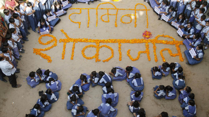 "Indian schoolgirls form numbers representing the year 2013 during a prayer ceremony in Ahmadabad, India, Monday, Dec. 31, 2012. The gang-rape and killing of a New Delhi student has set off an impassioned debate about what India needs to do to prevent such a tragedy from happening again. The country remained in mourning Monday, two days after the 23-year-old physiotherapy student died from her internal wounds in a Singapore hospital. Floral writing at the center reads ""Condolence to Damini,"" a symbolic name given to the victim. (AP Photo/Ajit Solanki)"
