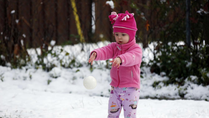 Molly Cleland, two and a half,  throws her own foam ball in favor to a snowball while playing in the snow in Jackson, Miss., Thursday,  Jan. 17, 2013.  A winter storm system left 2 to 4 inches of snow in parts of central Mississippi before heading east toward Alabama, the National Weather Service said. (AP Photo/Rogelio V. Solis)