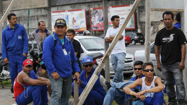 Workers from the Andrade Guiterrez construction company gather outside the Arena Amazonia stadium in Manaus