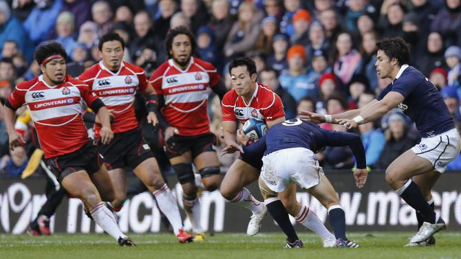 Japan's Fukuoka is tackled by Scotland's Laidlaw and Maitland during their rugby union match at Murrayfield Stadium in Edinburgh
