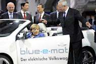 "German Chancellor Angela Merkel tries out an electric Golf convertible watched by CEO Martin Winterkorn during a visit to the Volkswagen plant in Wolfsburg on Monday. Europe's biggest car maker has announced that it got off to a ""successful"" start to 2012, with net profit nearly doubling in the first three months"