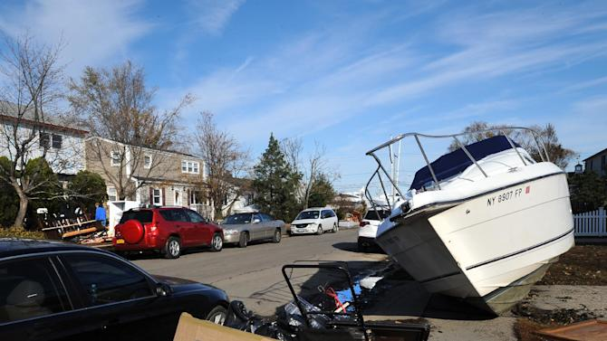 FILE - In this Monday, Nov 5, 2012 file photo, one of several boats that washed away from a nearby marina as a result of flooding from Hurricane Sandy and scattered throughout the yards of homes in Freeport, N.Y. Delegates from nearly 200 countries are meeting in the Qatari capital of Doha to discuss ways slowing climate change, including by cutting emissions of greenhouse gases that scientists say are warming the planet, melting ice caps, raising sea levels, and changing rainfall patterns with impacts on floods and droughts. (AP Photo/Kathy Kmonicek, File)