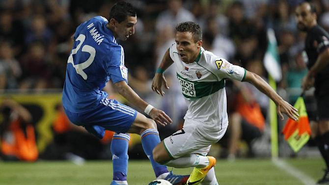 Real Madrid's Angel Di Maria from Argentina, right, duels for the ball with Elche's  Aaron Niguez Esclapez  during their La Liga soccer match at the Martinez Valero stadium in Elche, Spain, Wednesday, Sept. 25, 2013